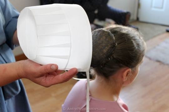 How do Amish women put up their hair?